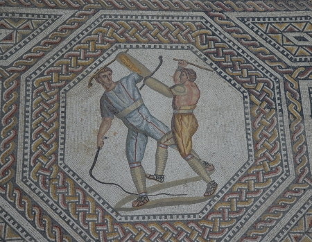 Two_combatants_attacking_one_another_with_cudgels_and_a_whip,_the_gladiator_mosaic_at_the_Roman_villa_in_Nennig,_Germany_(9288895115)